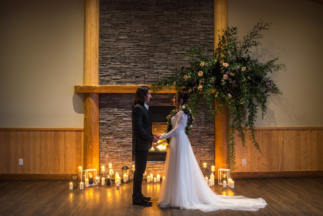 Newlyweds stand in front of large floral arrangement on fireplace mantle
