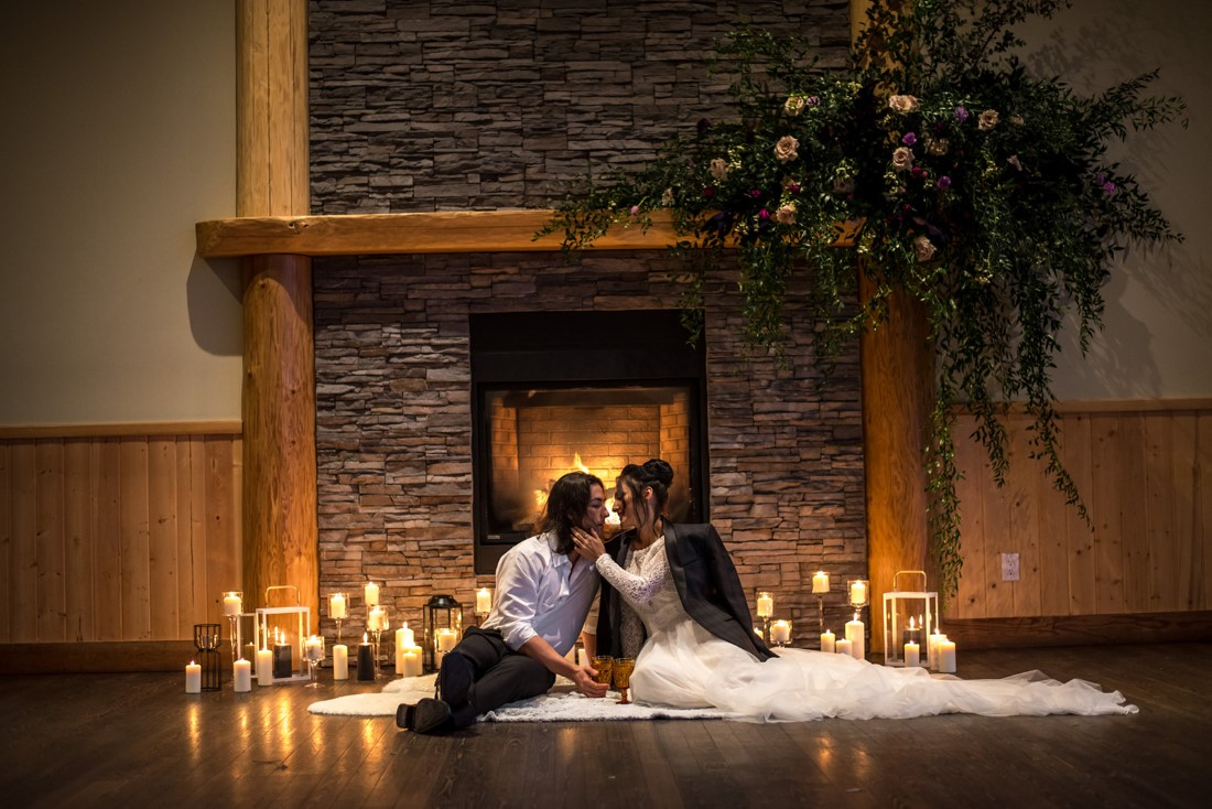 Eloping couples in front of fireplace surrounded by candles