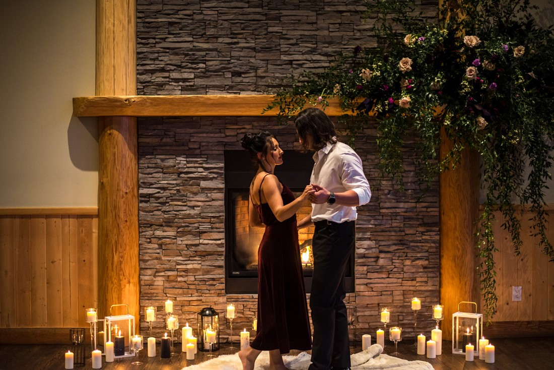 Cozy Elopement Inspiration couple in front of fireplace and candles