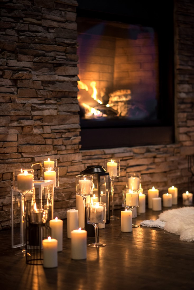 Candle holders sit in front of fireplace and white fur thorws by Nancy Bree PHotography