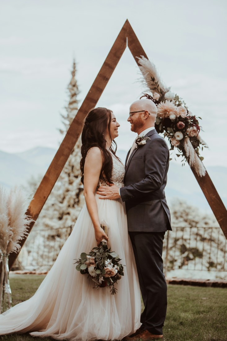 Wedding Vista with a View couple stand in front of A frame backdrop with flowers