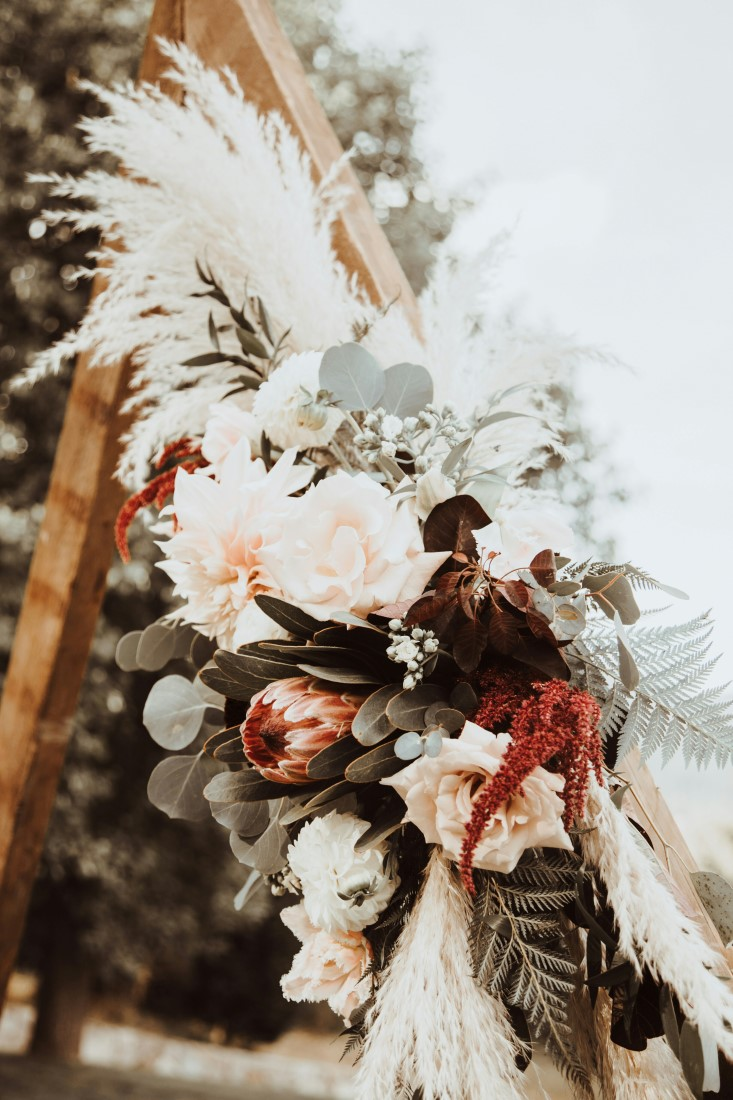 Burgundy and white flowers with eucalyptus on ceremony backdrop