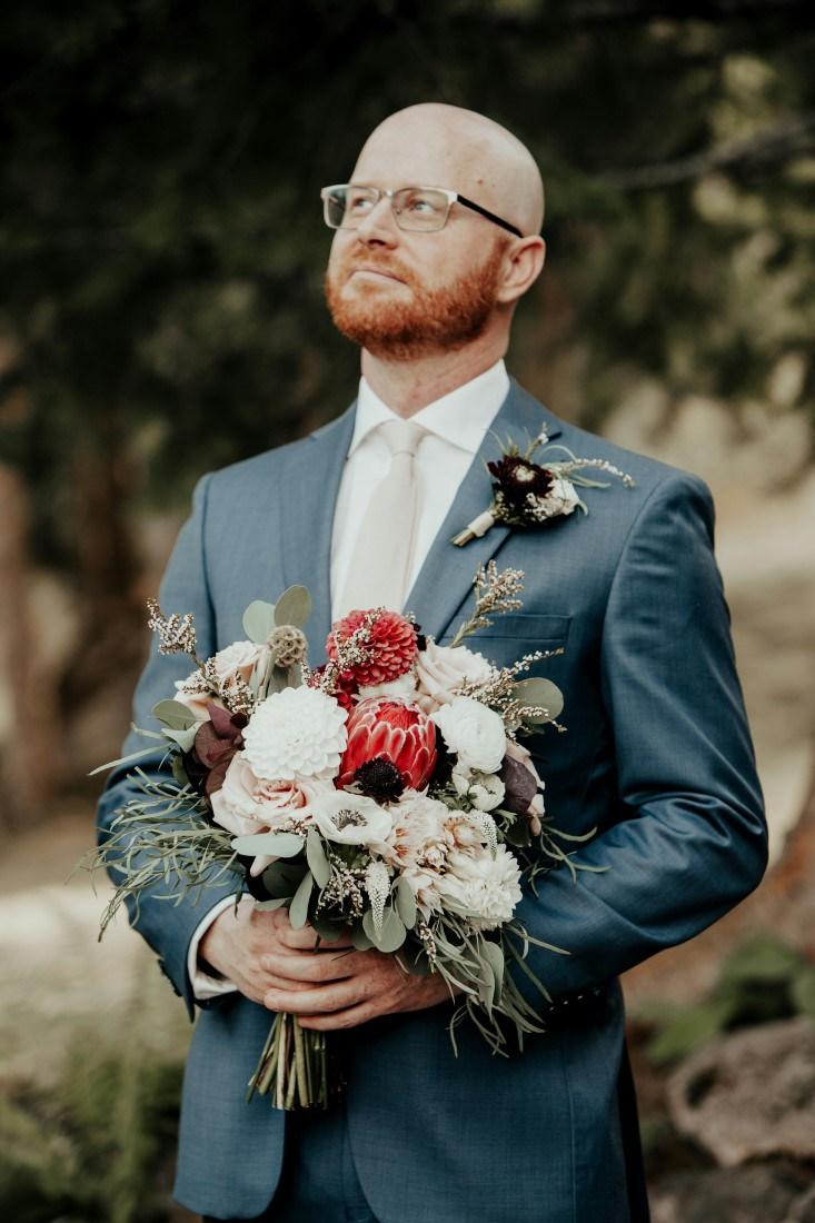 Groom holds bouquet of red and white flowers