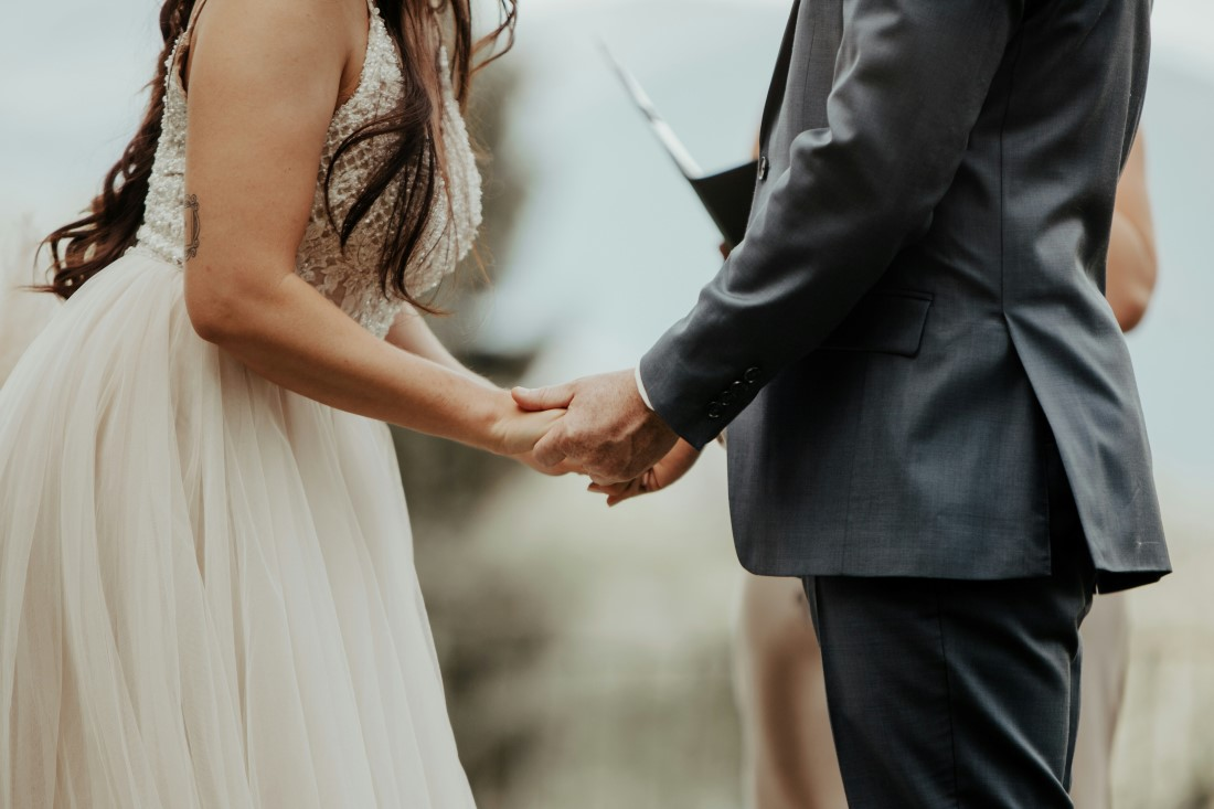 Bride and Groom hold hands while exchanging vows at Blaylock Mansion