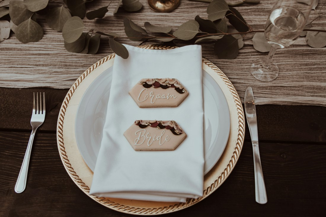 Beige plates sit on wooden wedding reception table