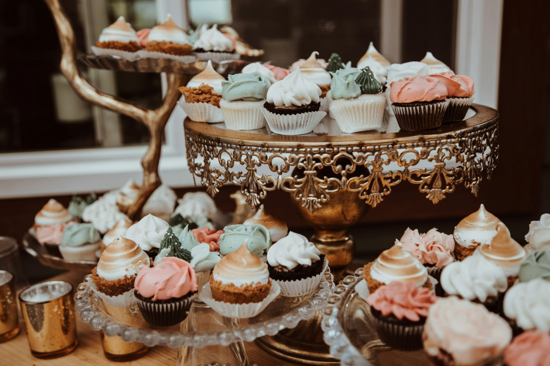 Cupcakes sit atop glass cake plates at wedding reception