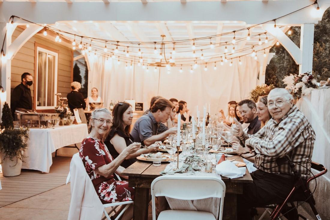 Guests sit at long table at wedding reception