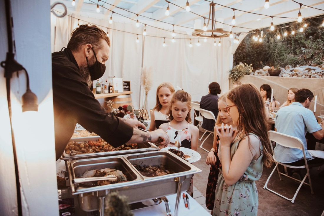 Children at wedding surround food table at reception