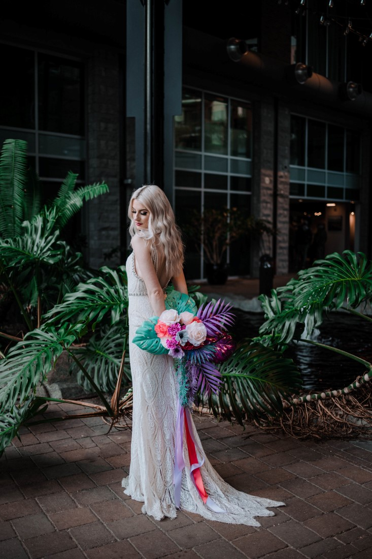 Bride holds bouquet behind her by Megan Maundrell Photography
