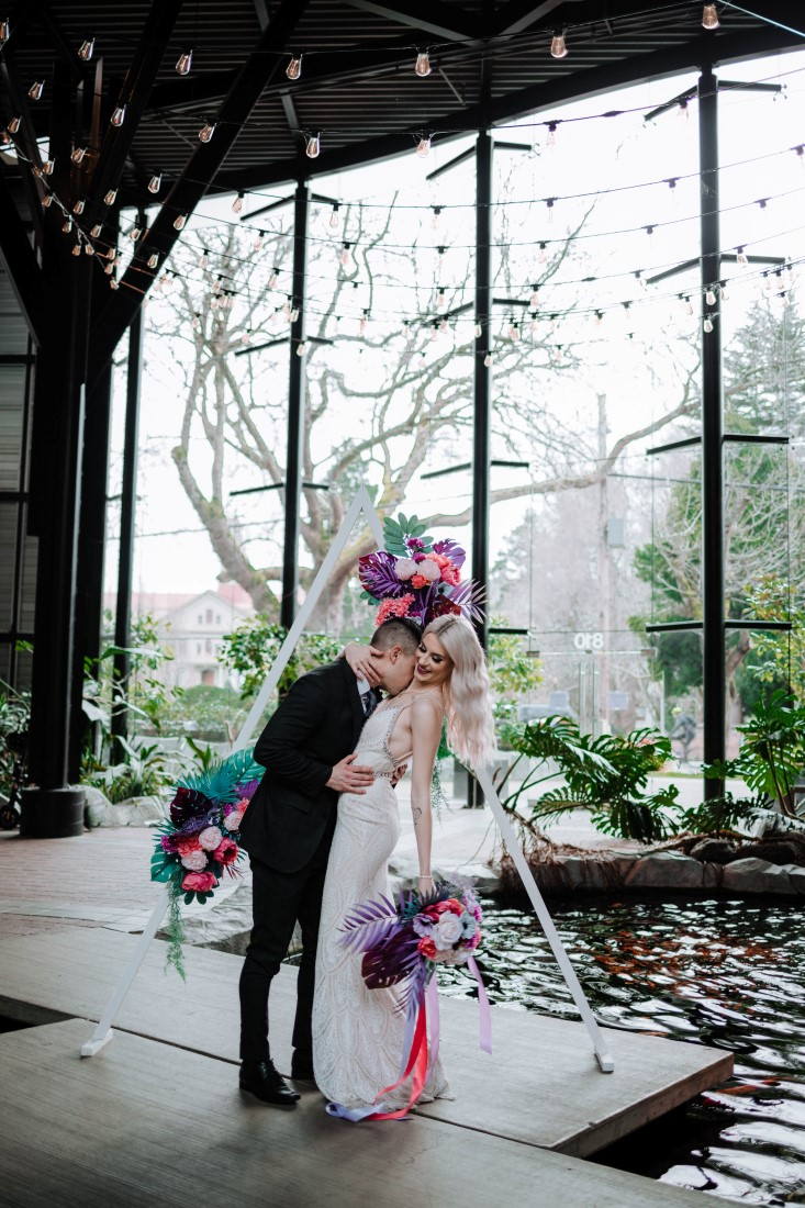 Newlyweds kiss after ceremony in atrium of Parkside Hotel