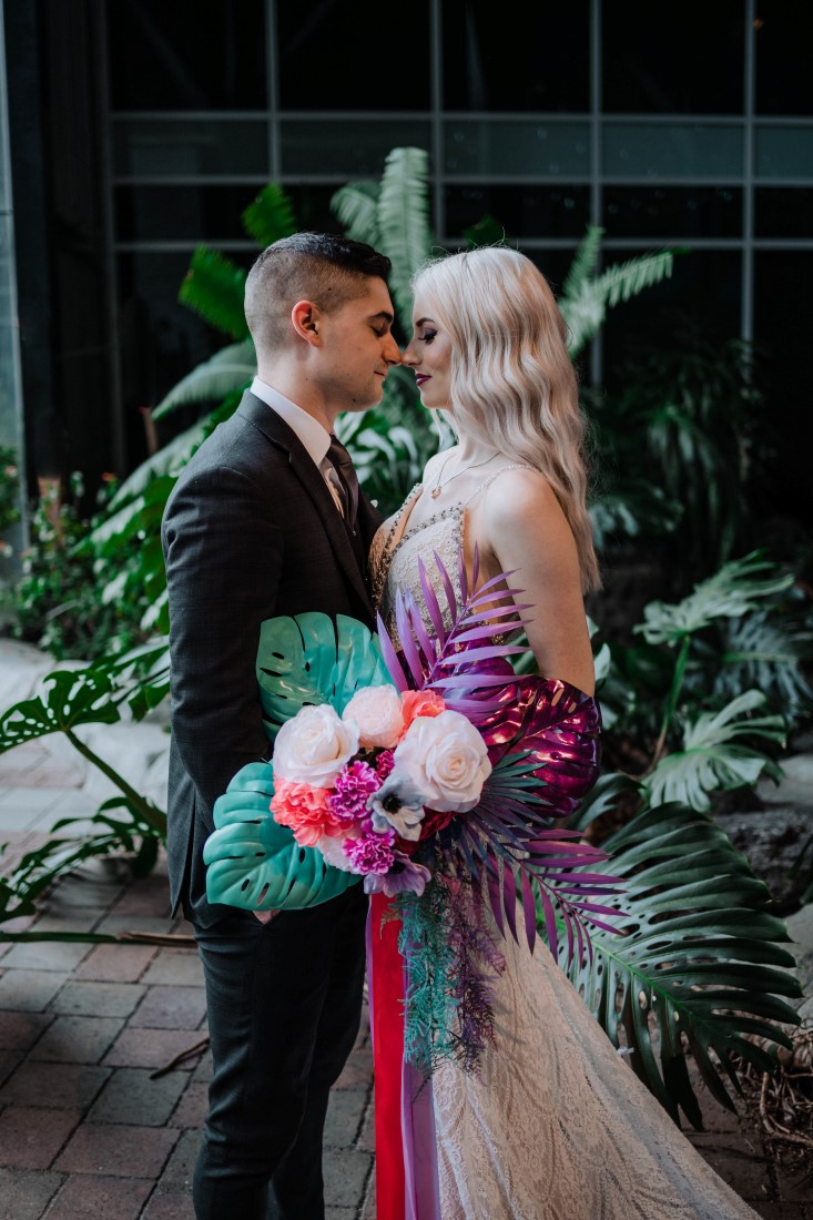 Newlyweds kiss behind the palms in the Parkside Hotel Atrium