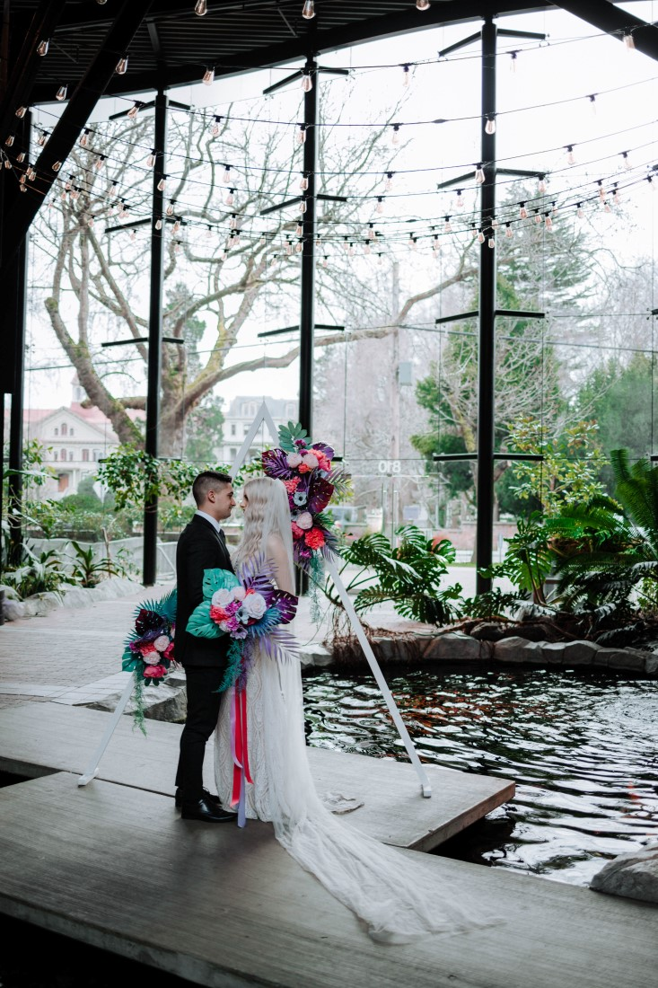 Wedding ceremony in front of triangle backdrop in atrium of Parkside Hotel