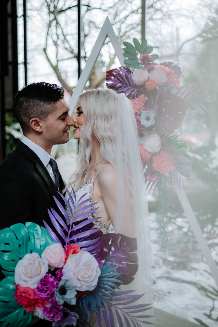 Newlyweds kiss in front of floral arrangement by En Vied Events