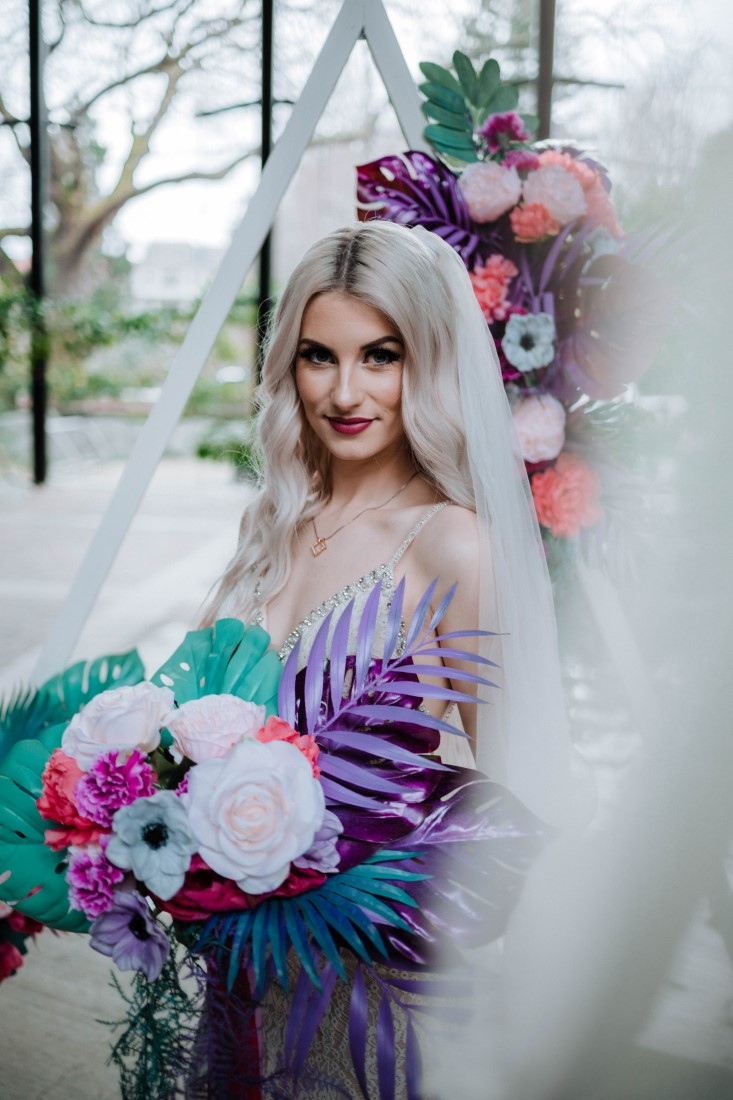 Bride holds couquet of teal, pink and white peonies and anemones by En Vied Events