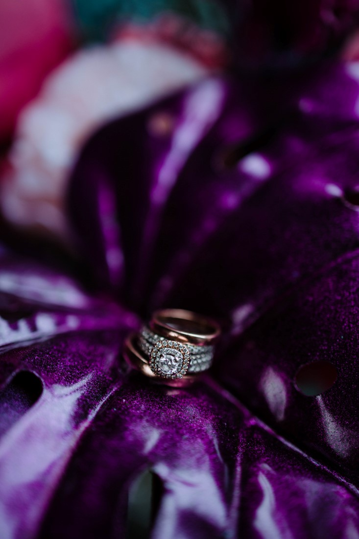 Diamond ring sits on purple palm leaf by En Vied Events