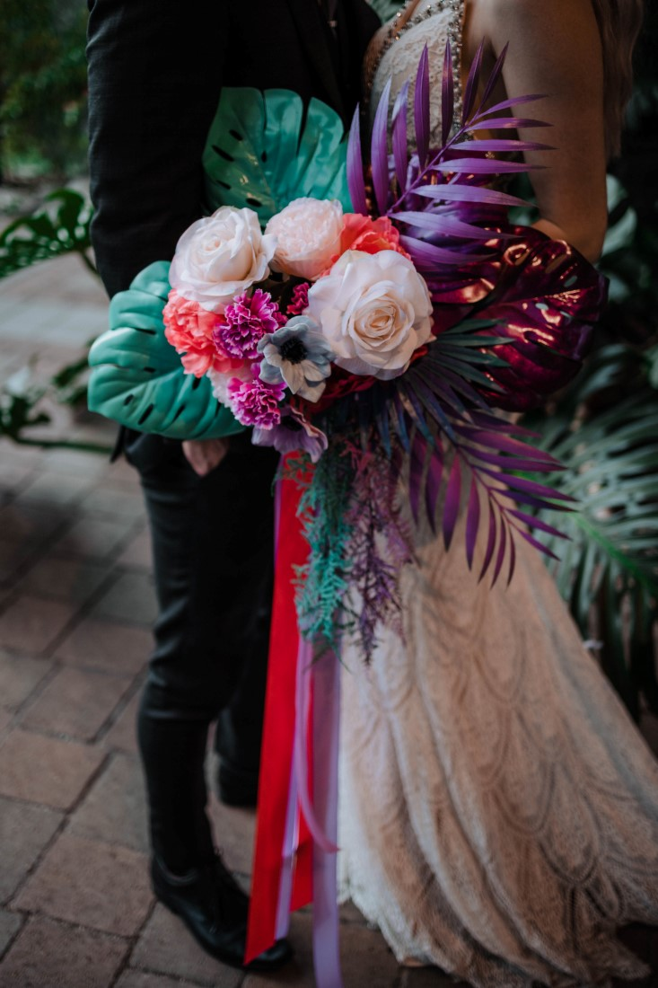 Pink and teal ribbons on bridal bouquet of peonies, carnations and palm leaves