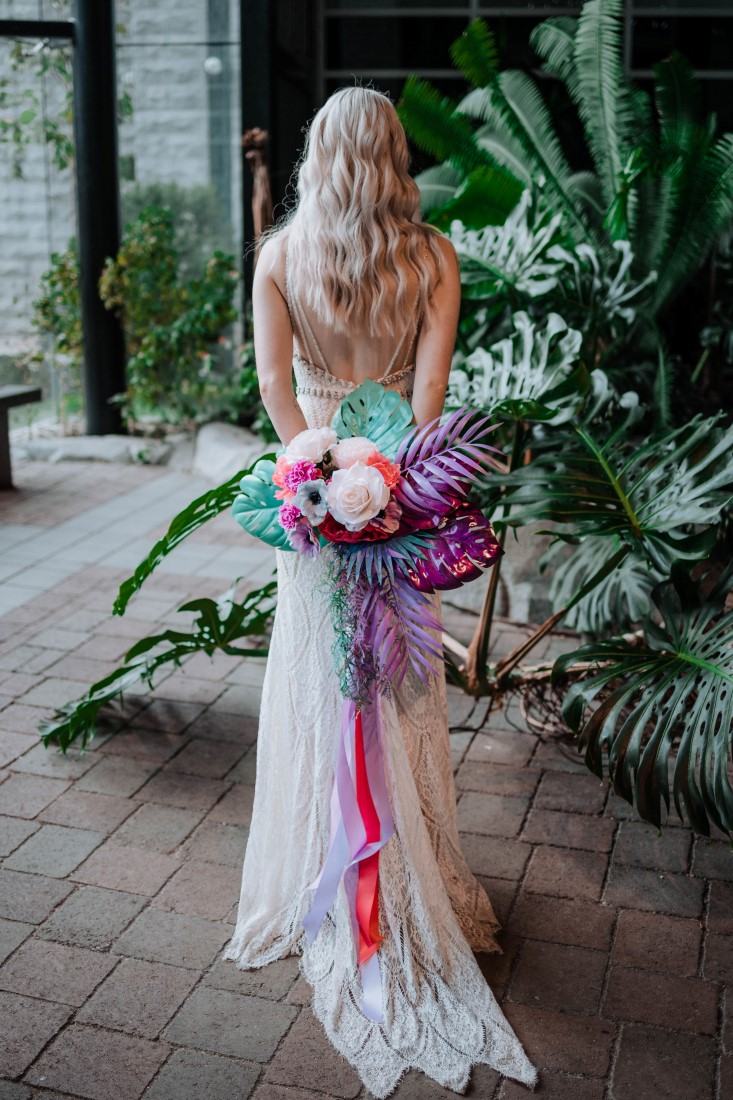 Elopement Giveaway bride holds bouquet behind her back with multicoloured ribbons
