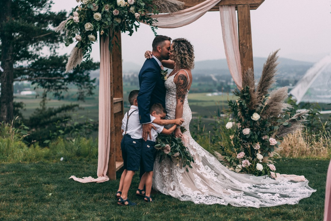 Love and Family Wedding couple kiss in fromt of weed backdrop covered in flowers