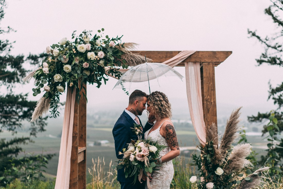 Newlyweds stand in front of wood backdrop with mountains behind