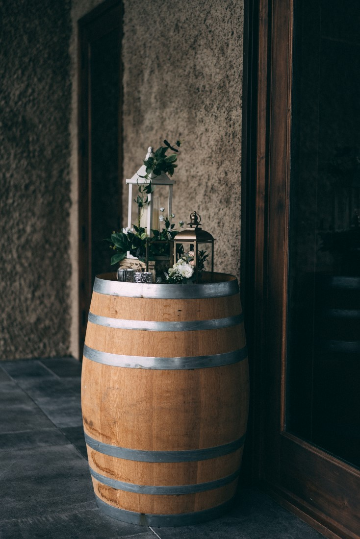Wood barrel with lanterns and greenery at wedding reception by The Little Wedding Shoppe Vancouver