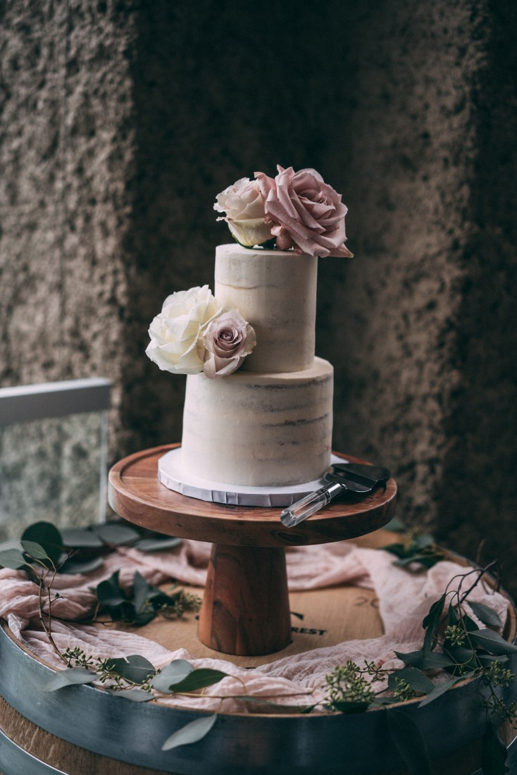Two tier white wedding cake with pink flowers on wood pedestal by Cake First Vancouver