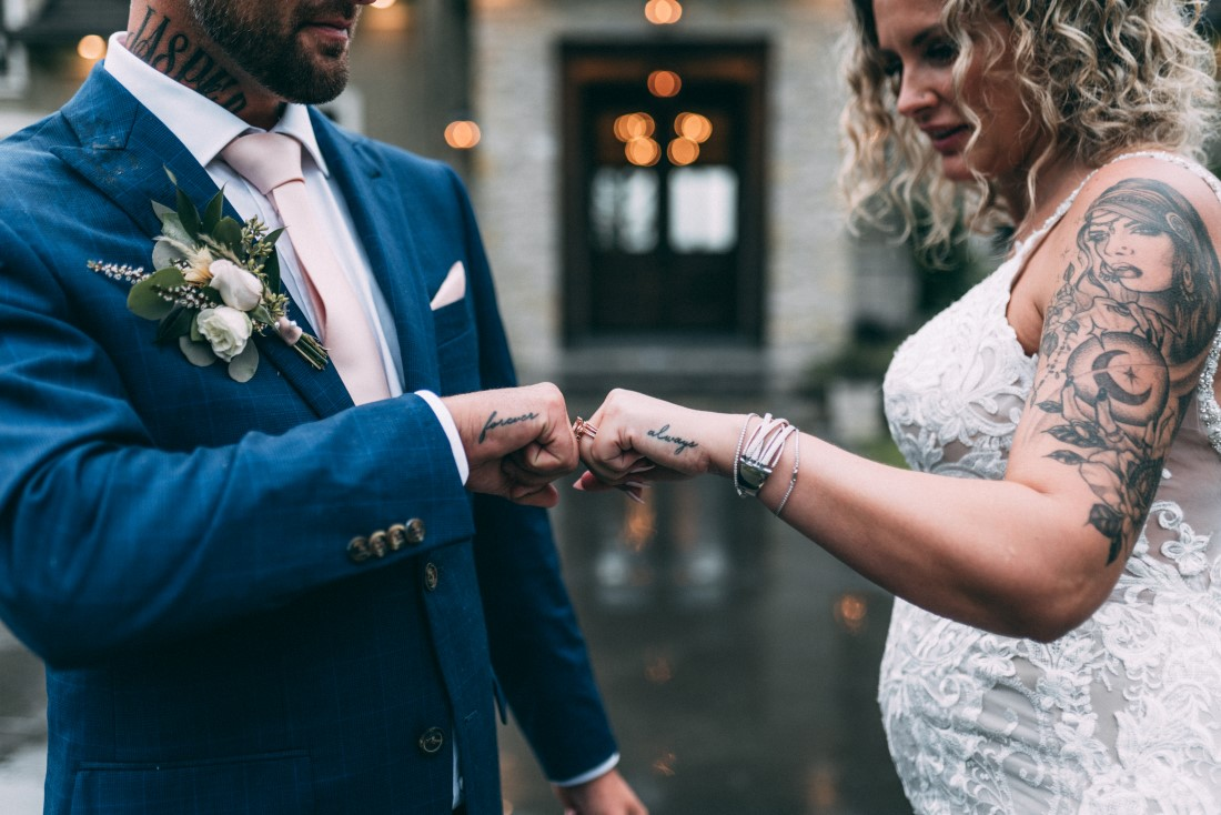 Newlyweds bump fists showing off wedding rings
