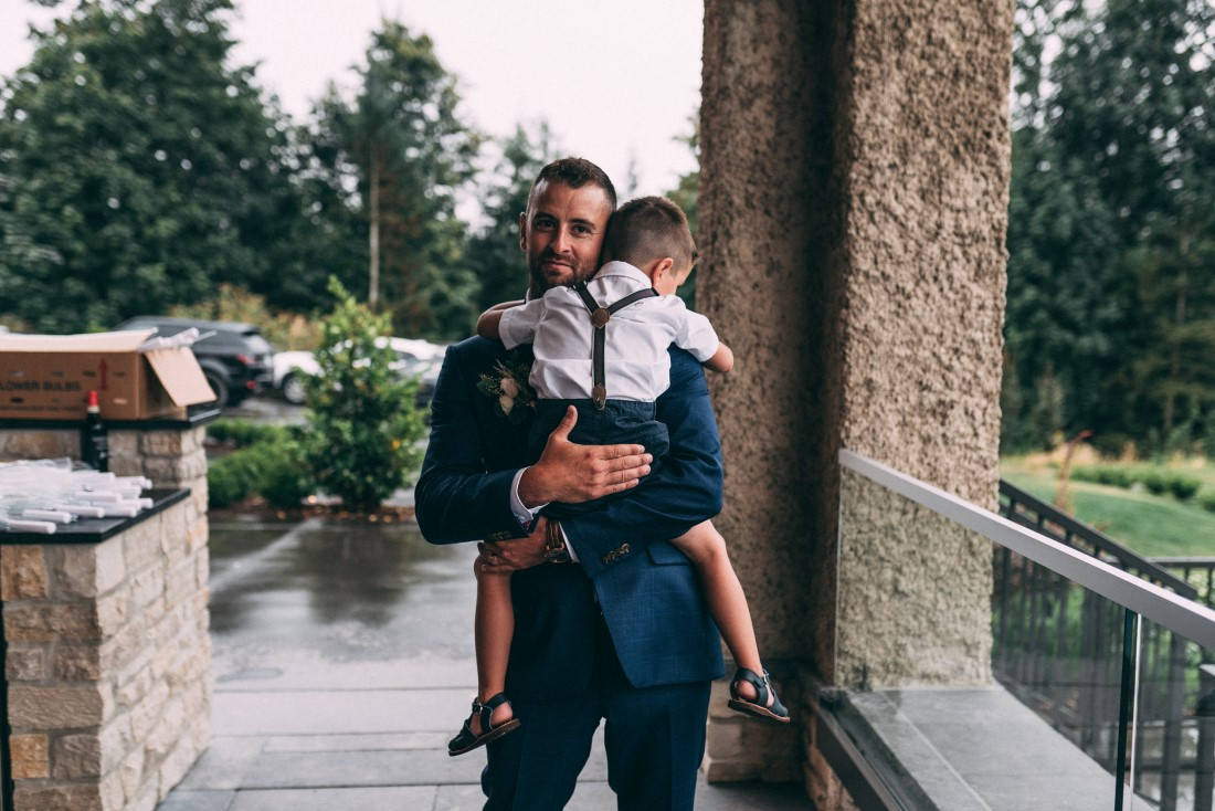 Groom holds tired young boy on wedding day