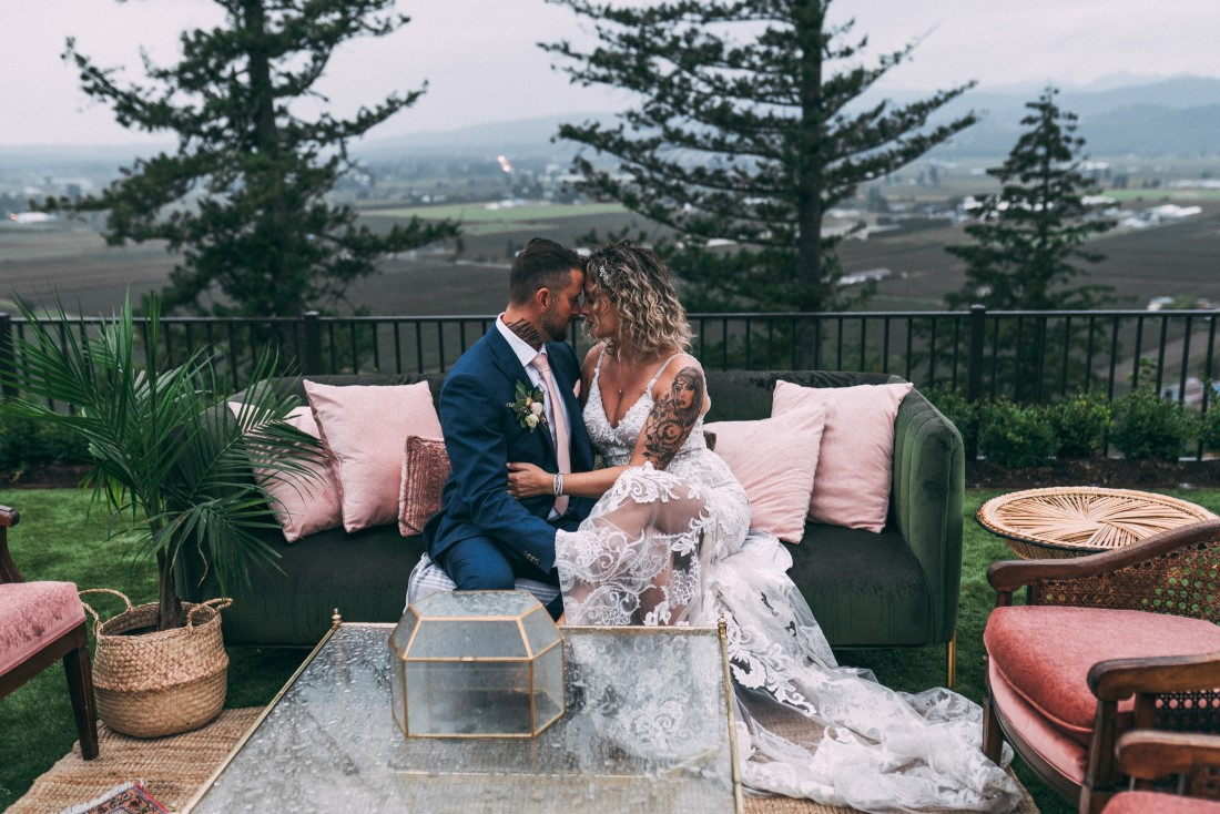 Newlyweds sit on couch with trees and mountains in the background by Vancouver