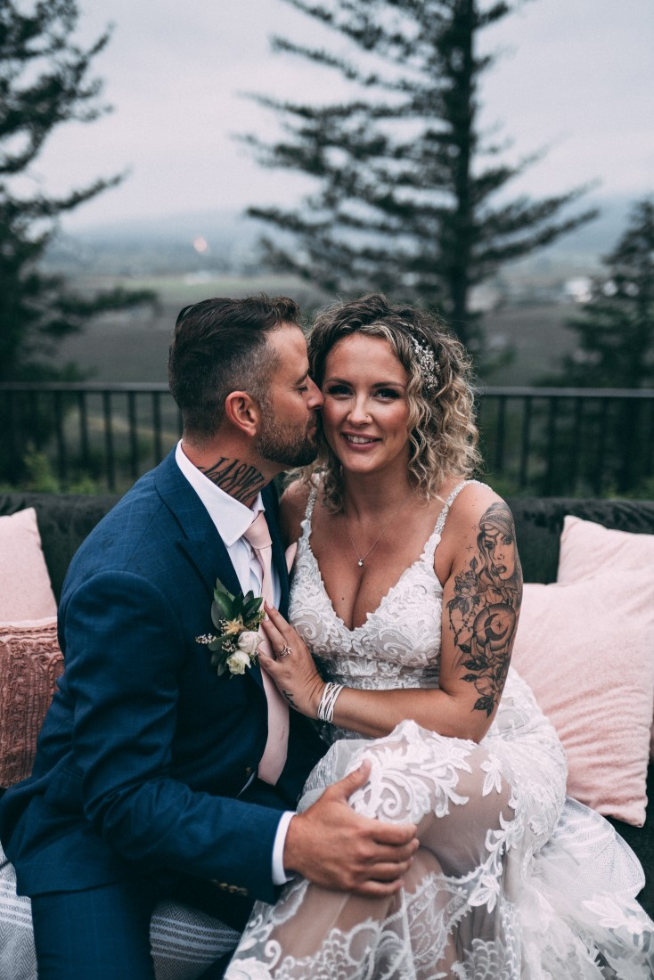 Groom kisses bride on the cheek by The MacLeans Vancouver