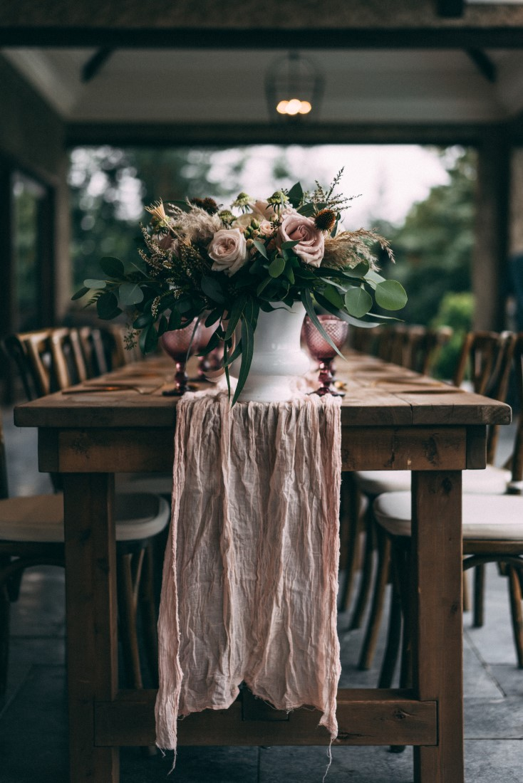 Blush pink runner falls over edge of wood table with pink and white flowers by AJR Designs Vancouver
