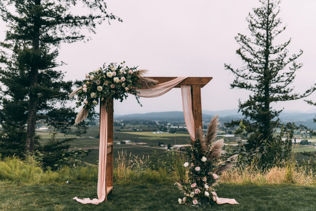 Wood ceremony backdrop covered in white fabric and floral with mountains behind by AJR Floral Design Vancouver
