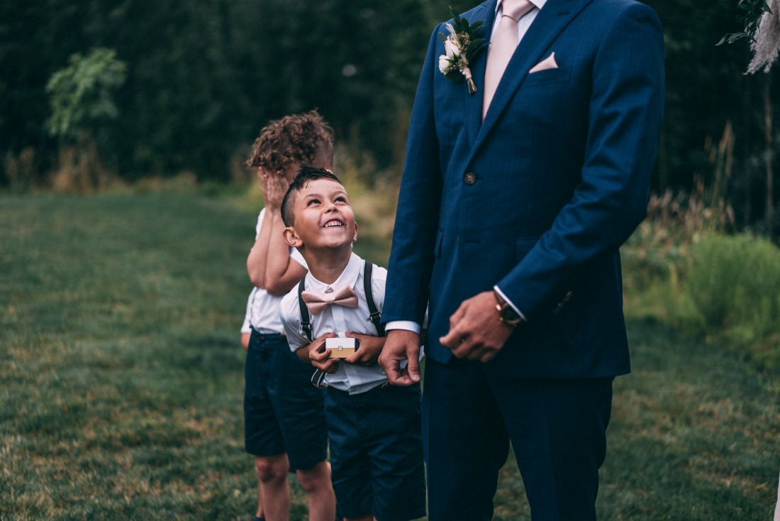 Little boy looks up at groom while they await the bride