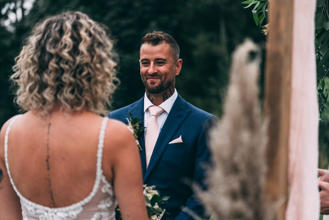 Groom looks at bride while exchanging wedding vows