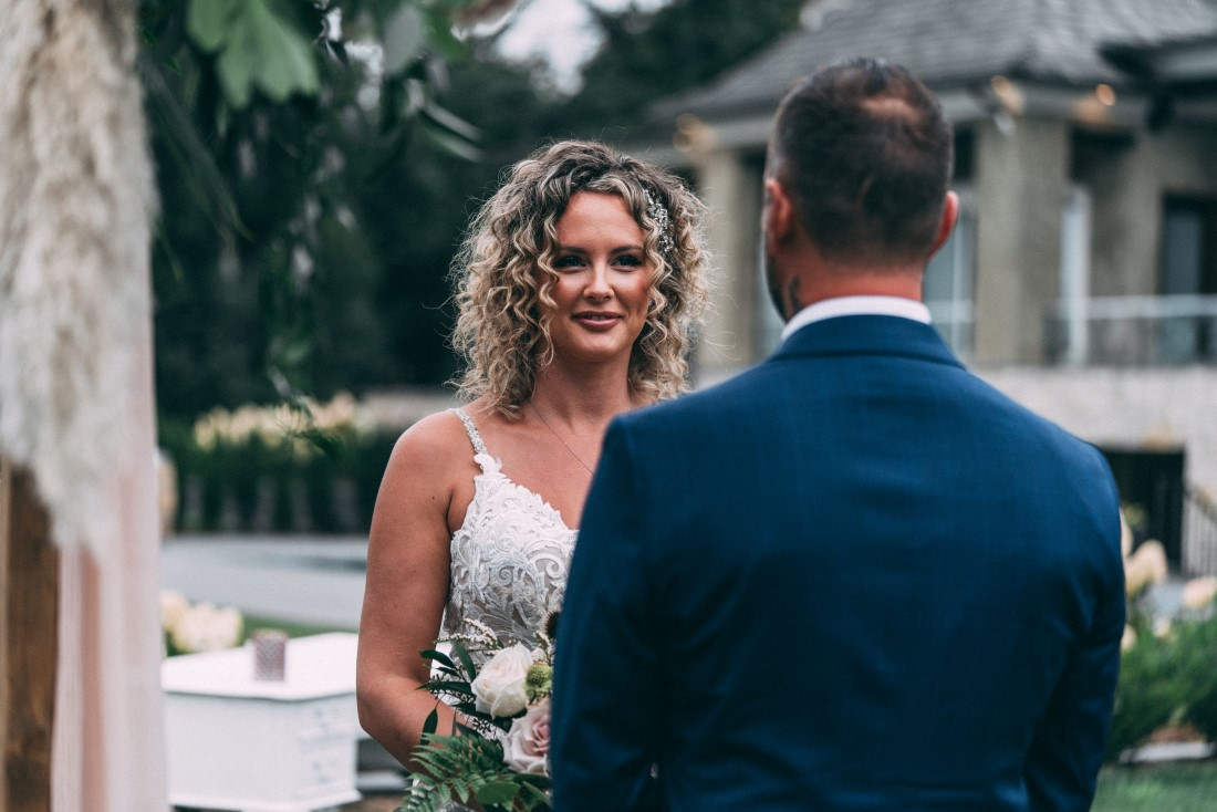 Bride looks at groom as vows are exchanged at wedding ceremony