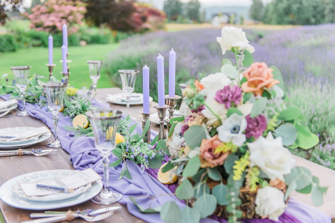 Lavender runner and candles among brightly coloured flowers on wood talbe in lavender field by Vancouver