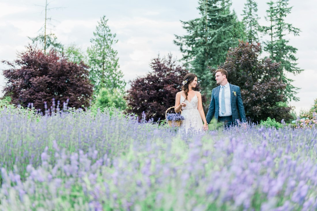 Bride and groom walk through field of lavender by Lestelle Photography