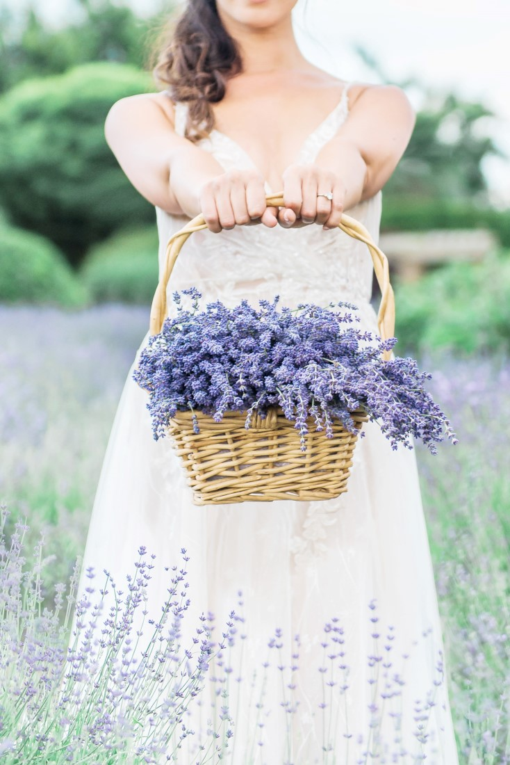 Bride in Pronovias gown holds out basket of lavender