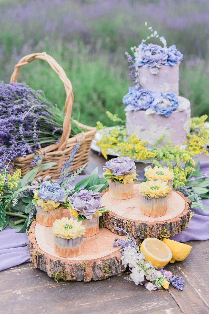 Cake, cupcakes and lavender sit on wood rounds on wedding reception table