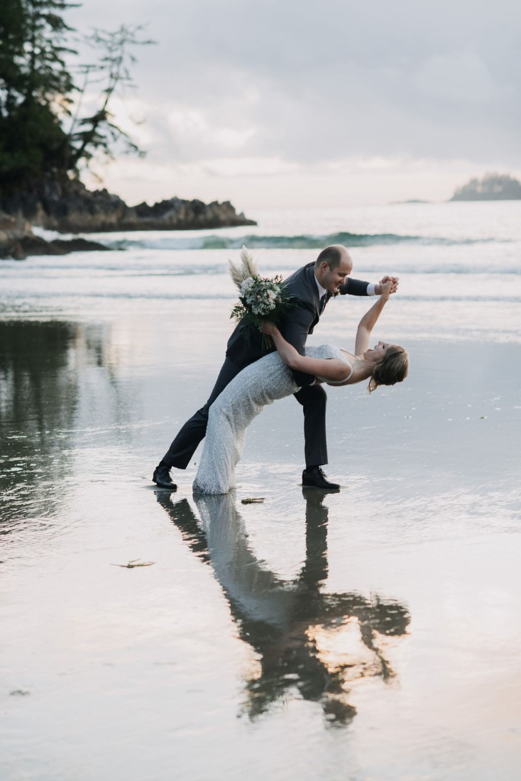 Groom bends his bride backwards on Tofino Beach by Bracey Photography