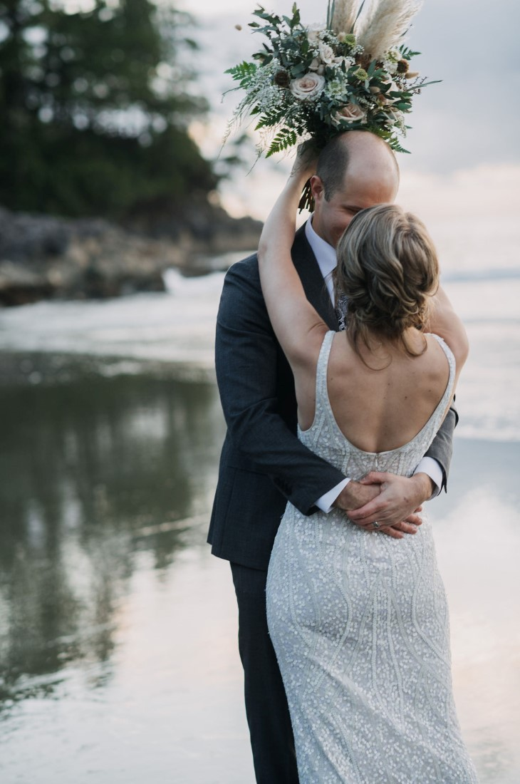 Newlyweds kiss with bouquet behind grooms head in Tofino British Columbia wedding