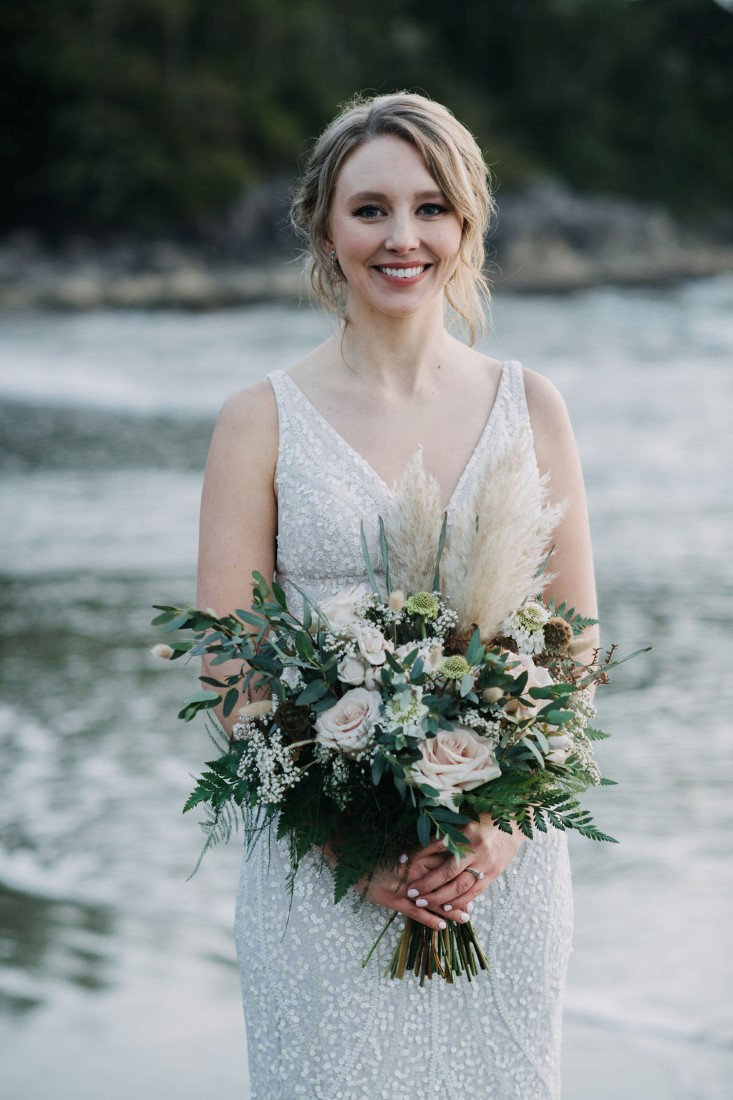 Bride in lace gown holds bouquet of ferns and roses by Crab Apple Floral Tofino