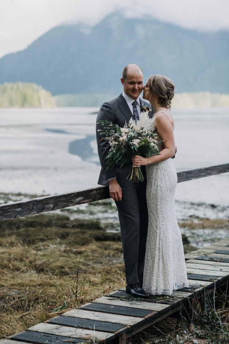 Newlyweds stand on wood sidewalk near Cedarwood Cove Tofino