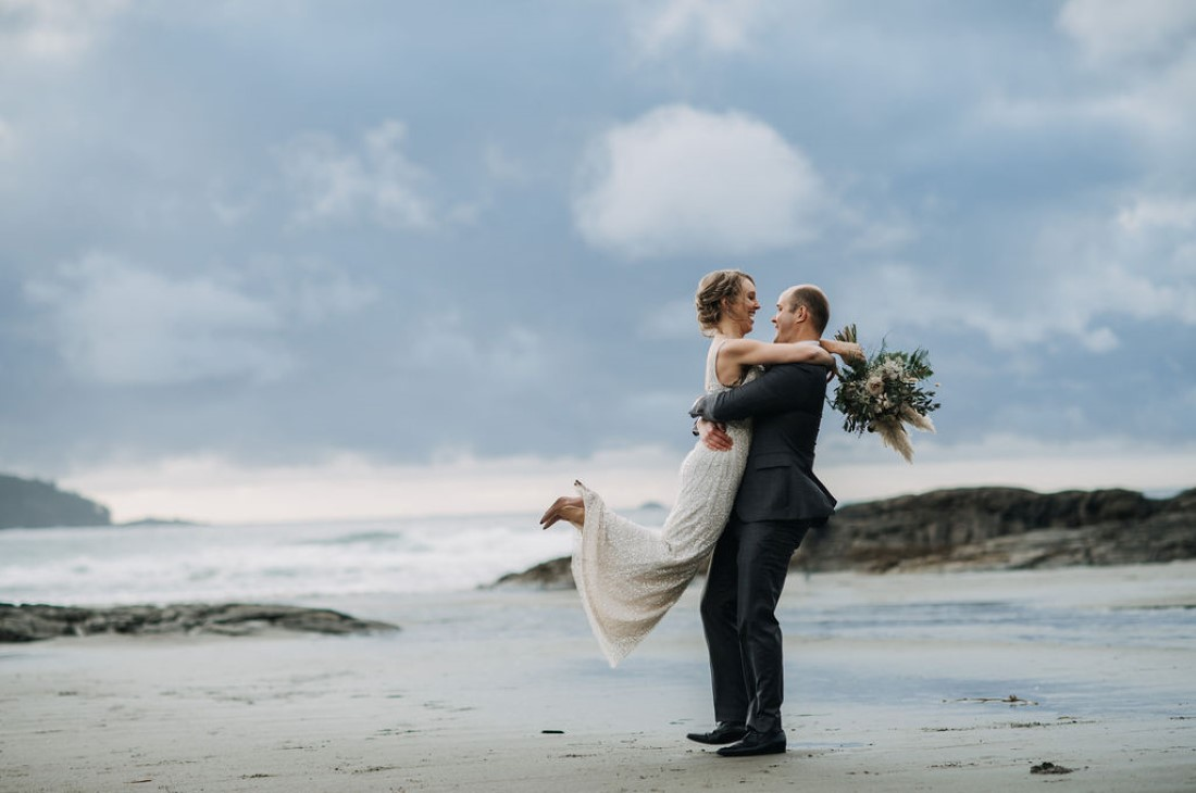 Groom picks up his new wife on the Tofino Beach Vancouver Island
