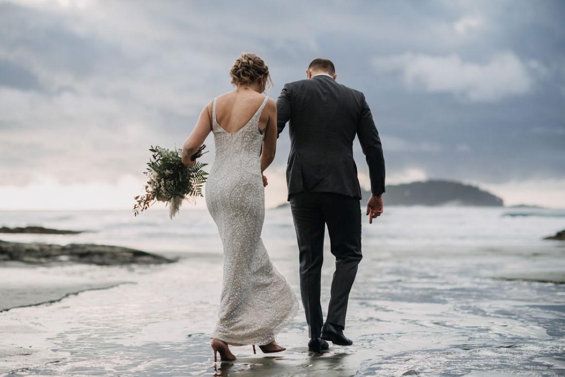 Newlyweds walk across the waves on Tofino Beach near Cedarwood Cove Cabin