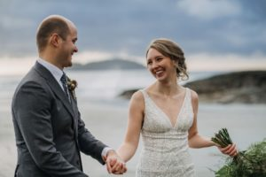 Bride smiles at her groom and holds bouquet on the beaches of Tofino
