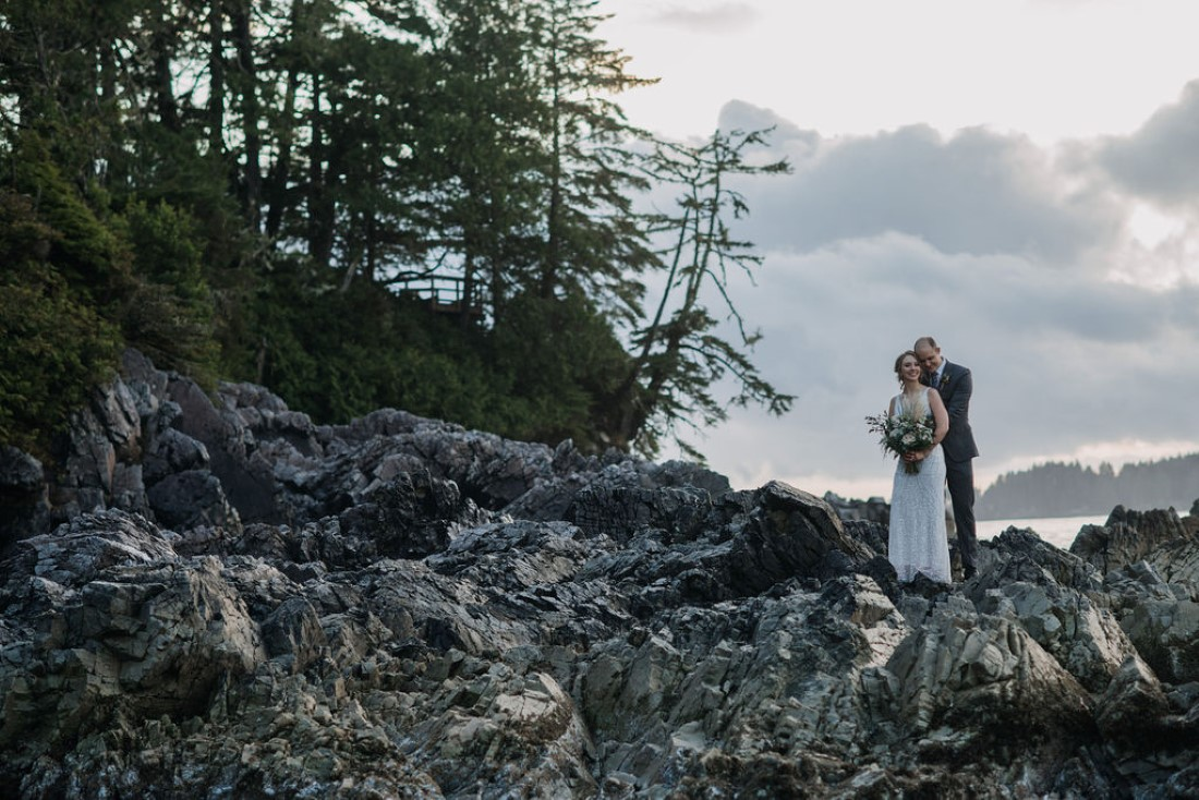 Newlyweds stand on black rock with trees and ocean behind them in Tofino
