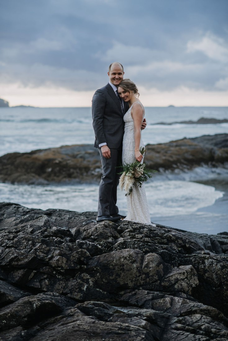 Newlyweds stand on black rocks of Ucluelet by Bracey Photography