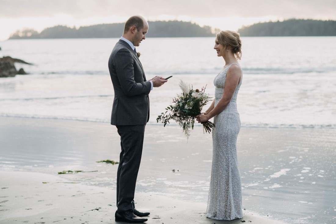 Groom reads his wedding vows to bride on Tofino beach by Bracey Photography