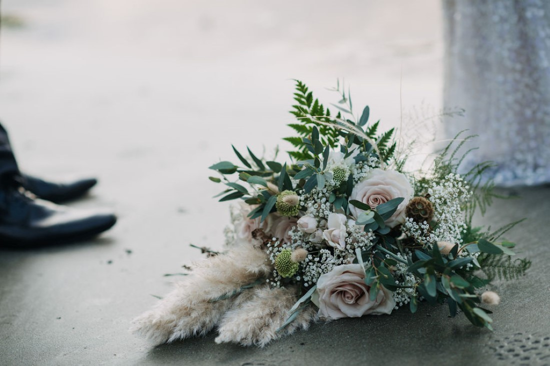 Bouquet of ferns, roses and dried grasses on beach sand by Crab Apple Floral Tofino