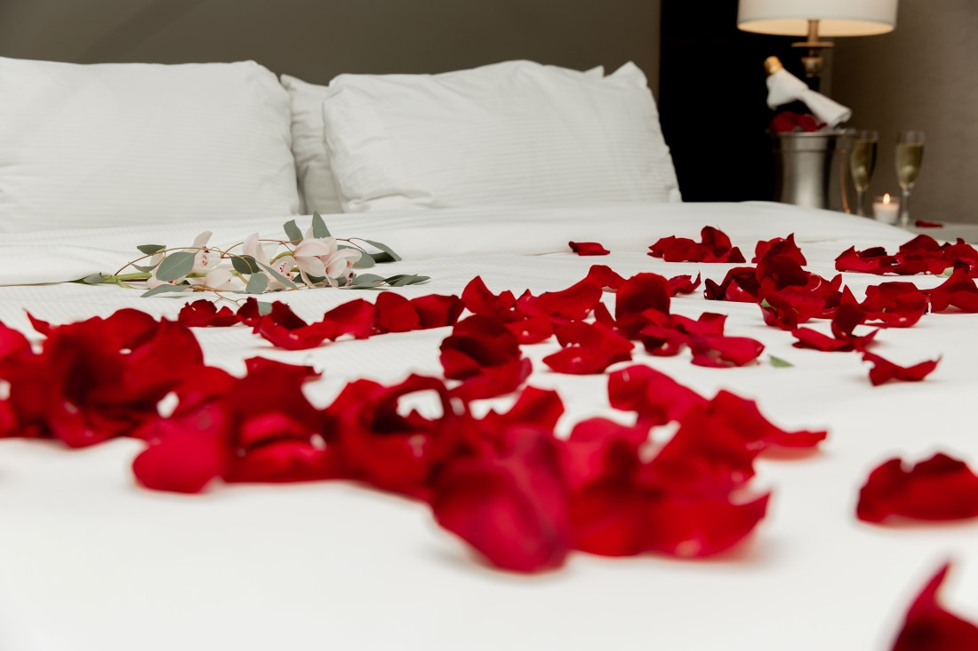 Rose petals on white bed at Vancouver Hilton